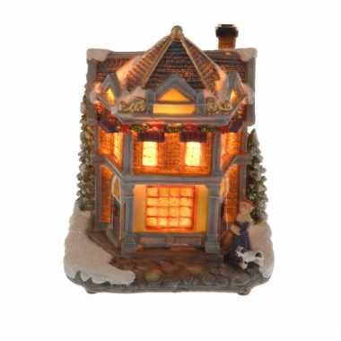 Kerstkerstdorp huisje met vrouw en hond met verlichting