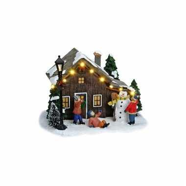 Verlichte kerstkerstdorp huisjes met sneeuwpop
