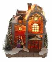 Kerstkerstdorp huisje met vrouw en kind met verlichting